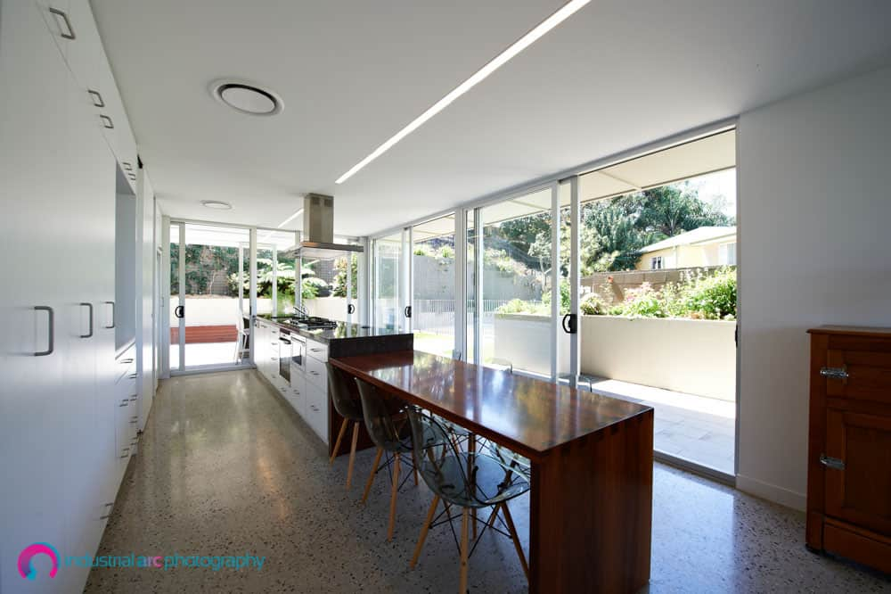 Interior of architecturally designed house in QLG, showing kitchen bench extending from the interior to the exterior