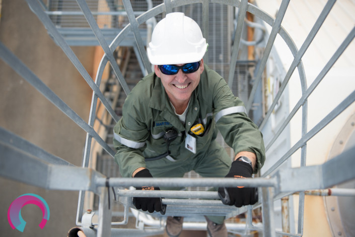Image of man in hard hat, photographed from above, climbing up a set of industrial stairs