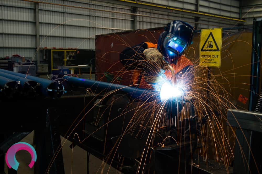 Person conducting arc welding with sparks visible in the image