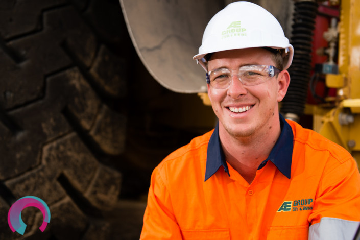 Industrial portrait of a male engineer in a hard hat, safety glasses and high visibility shirt photographed sitting down in front of a large truck tyre