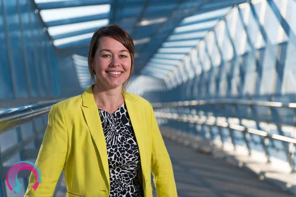 Portrait image of woman in yellow jacket with architectural detail behind her (Ipswich Motorway Overpass, blue steel structural detail)