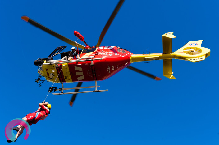 Westpac Rescue Helicopter with crew member being winched, photographed from the ground looking up
