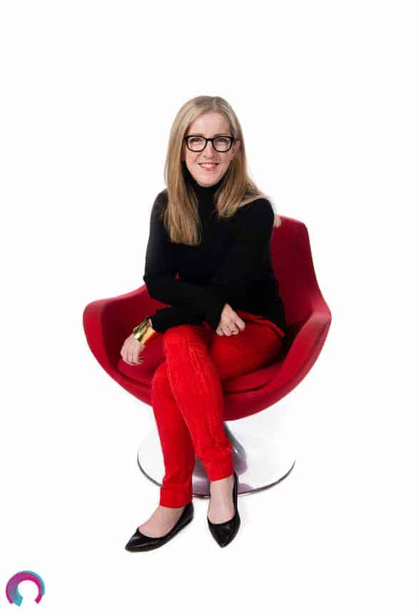 Corporate portrait of a female Brisbane executive wearing red pants and a black shirt, seated on a red chair, facing forward, leaning into the camera