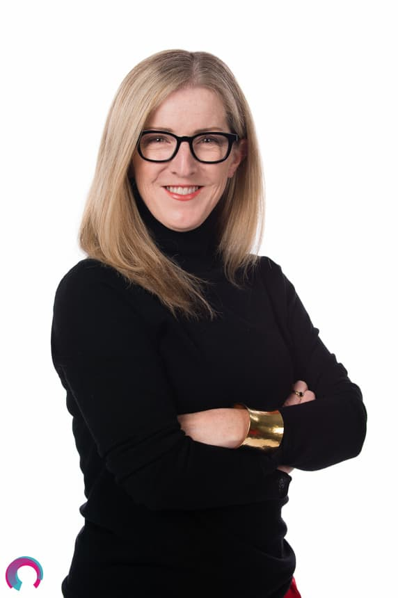 Corporate portrait of a female Brisbane executive cropped at the waist, black shirt arms folded smiling.