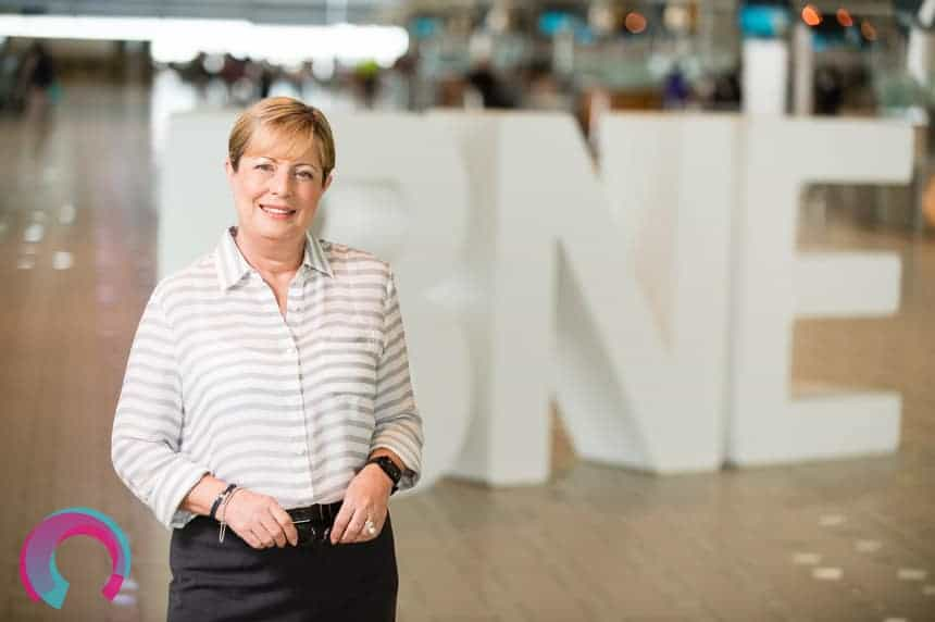 Corporate portrait of Julieanne Alroe, standing in the International Terminal Brisbane Airport, with three giant letters behind her. Letters are 'BNE""