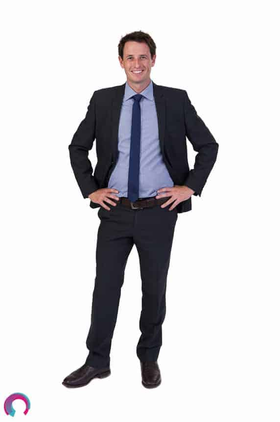 Full length corporate portrait of man wearing a dark suit, blue shirt and blue tie, facing camera, hands on hips, smiling, looking relaxed.