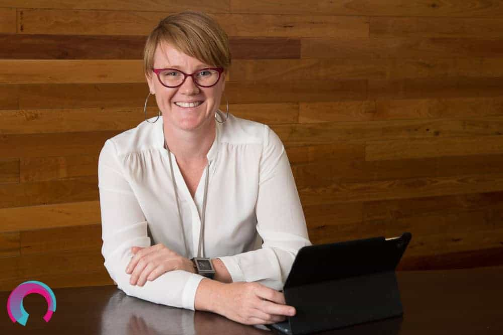 Jen Dainer, commercial portrait photographer, sitting in front of a timber wall, seated at a desk.