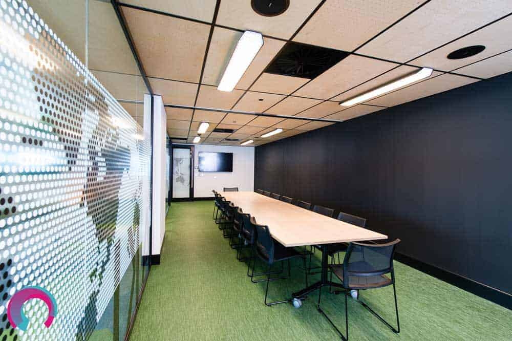 Meeting room showing long timber desk with black chairs and green carpet, with glass walls on one side, showing map of world on the glass. Black wall on opposite side - commercial office photography Brisbane