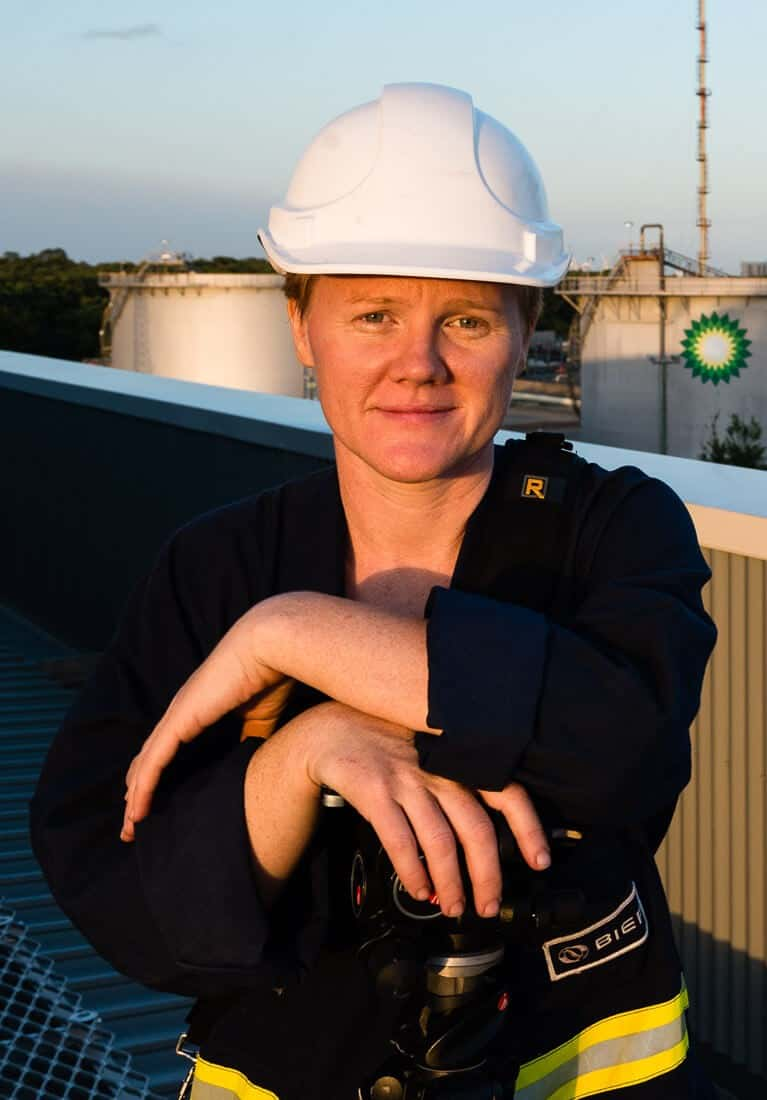 Portrait of industrial photographer and video producer, Jen Dainer, in safety hard hat and overalls, shot on an industrial site in Brisbane