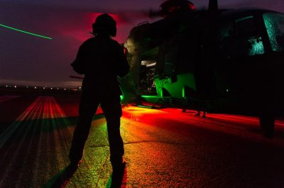At dusk you see the silhouette of an MRH90 military helicopter from the side. In front of the helicopter you can see an aircrewman with flight suit and helmet standing with their back to the camera. The red and green ground lights of the MRH are visible, casting a green and red glows on everything. The piano keys (white landing strips of the runway) are visible beneath the MRH. The green tip lights of the helicopter are visible and we can see that the rotor blades are turning, as there is a trail of light caused by the movement of the rotor blades through the air