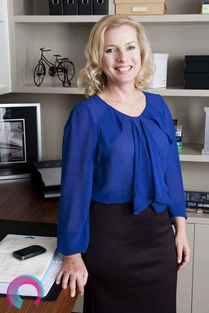 Smiling blonde woman in blue top and black skirt standing at an office desk in front of a shelving unit full of books and personal items