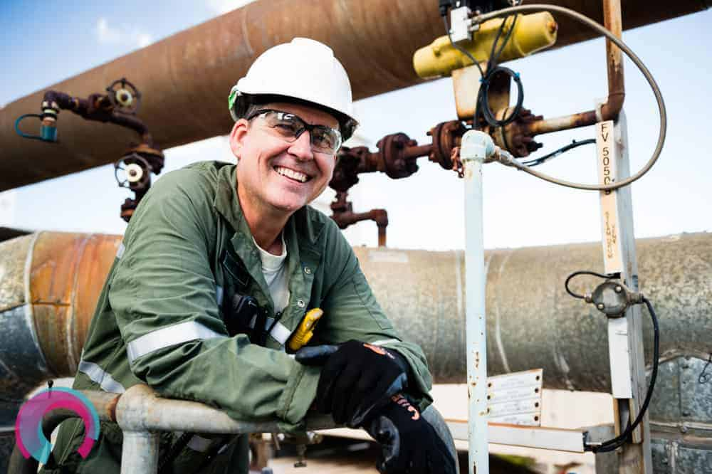 Smiling man in green overalls, hard hat, safety glasses and gloves standing underneath a large rusted pipe on a sunny day with blue sky