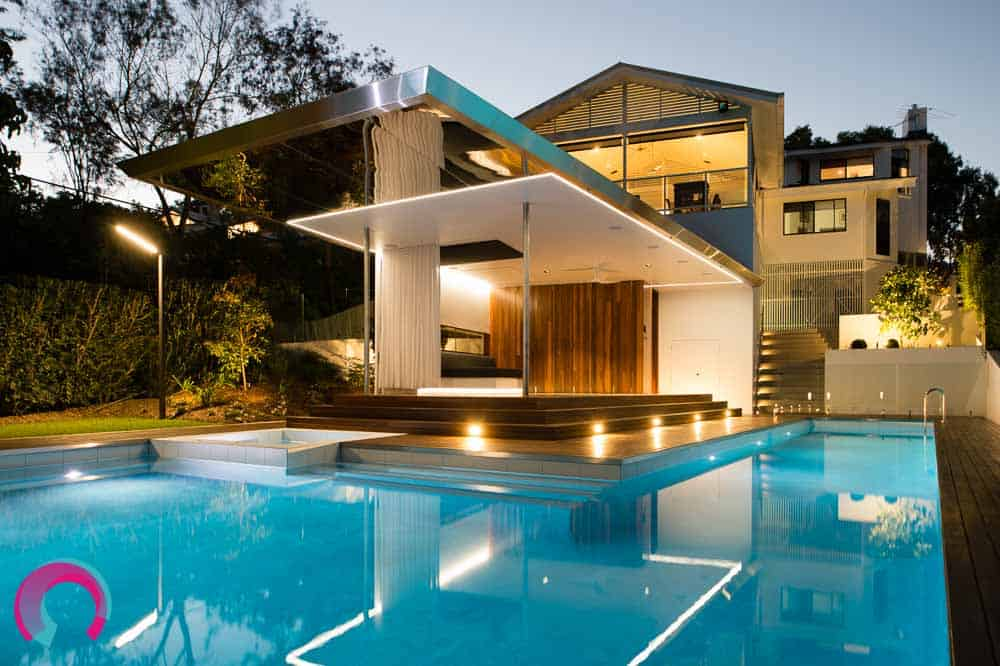 Exterior architecture photography of a residential pool pavilion redesign by Tektonika Architects, showing how the pavilion attaches to the three story house behind it.