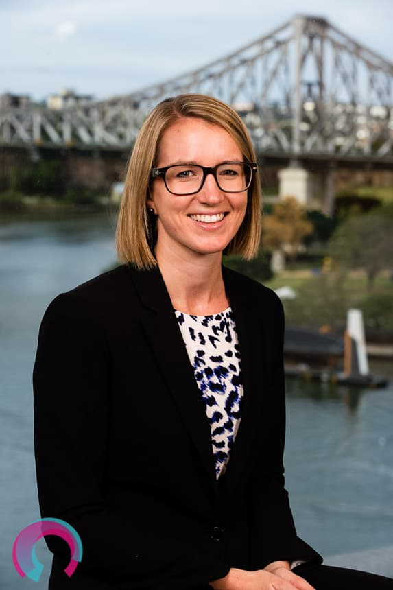 Corporate portrait of a blonde female with glasses sitting down, with Brisbane's Story Bridge as the background