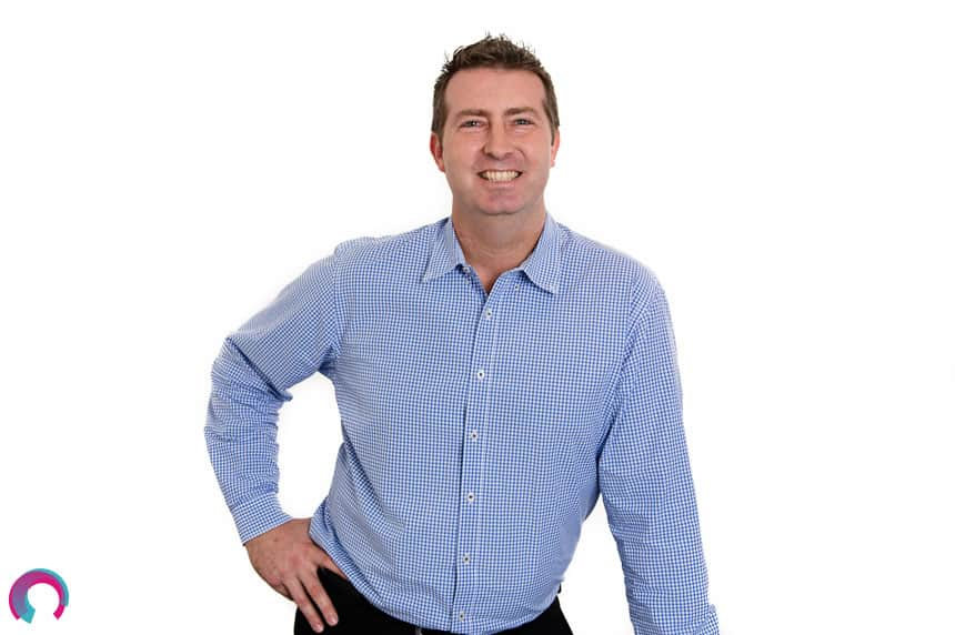 Corporate portrait of man in blue business shirt standing against a white background, leaning on a chair that is just out of frame