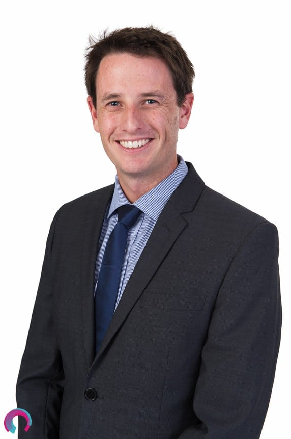 Corporate portrait of a male Brisbane Executive shoulders turned to the left of frame, wearing a suit and tie, smiling naturally