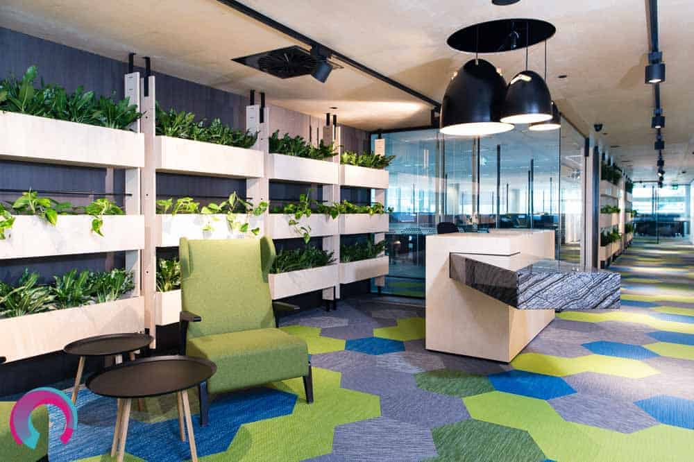 Reception area for commercial office showing geometric shapes and lovely marble reception desk, with hanging pendant lights. Wall of green plants behind reception desk - commercial office photography Brisbane