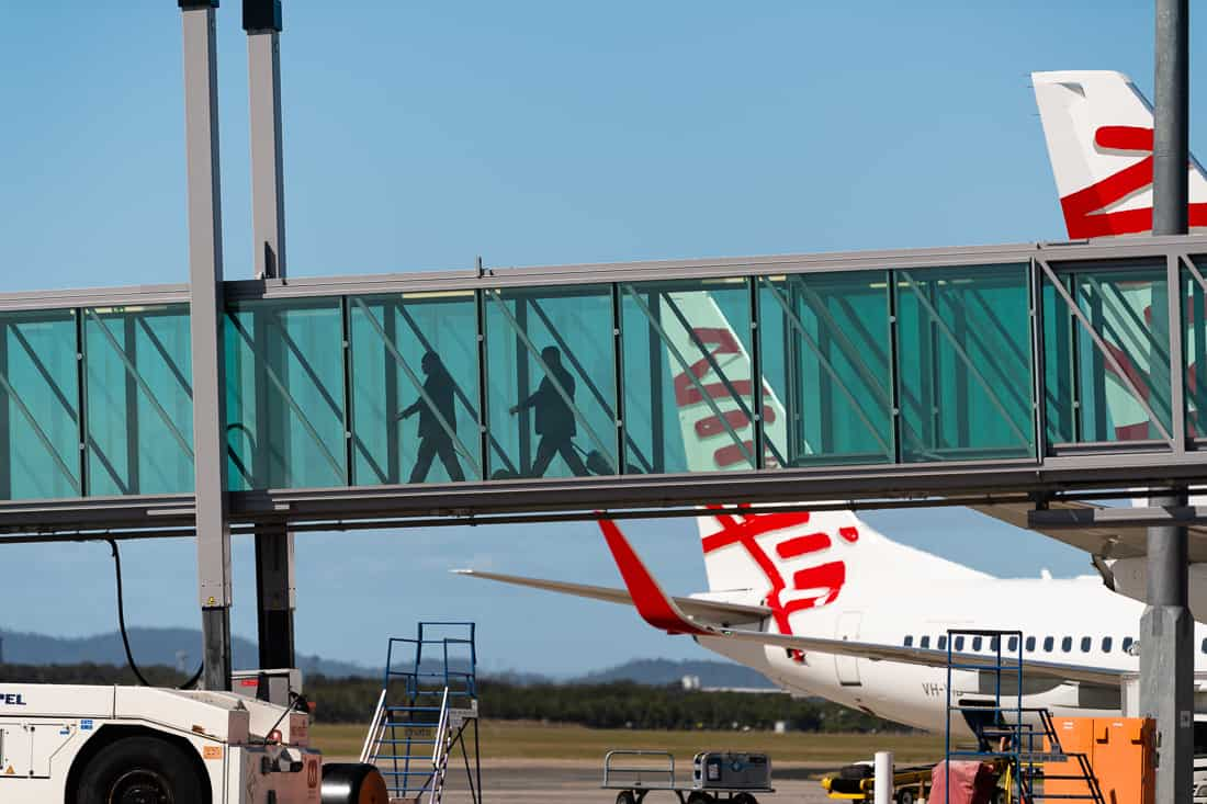 Two passengers walking down a glass aircraft gangway towards an aircraft with two Virgin aircraft tails in the background