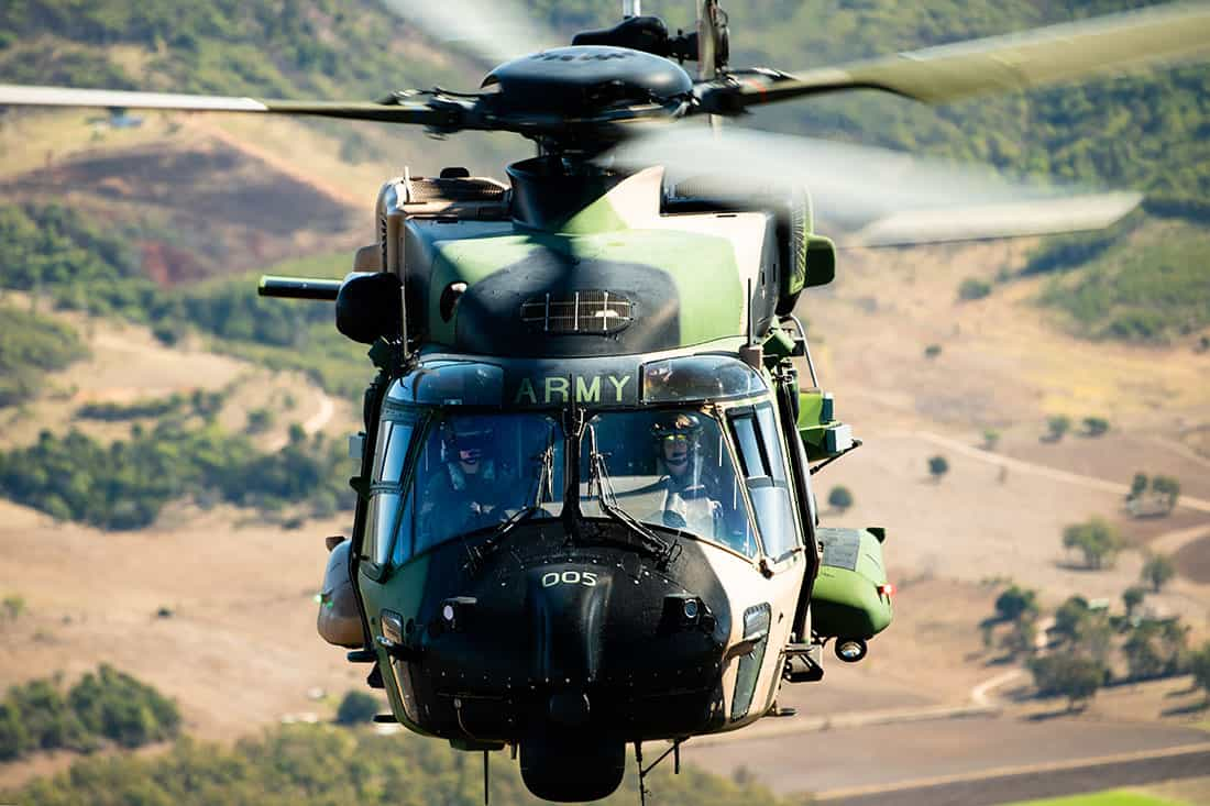 Close up of an Australian Army MRH Taipan Helicopter in the air, photographed from above, showing both pilot's faces, shot from the ramp of another MRH