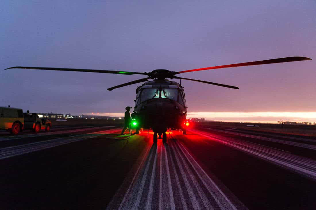 MRH90 military helicopter, lined up on the piano keys (white runway lines) of a runway at Oakey Airport at dusk. Red and green lights on the body of the MRH cast a glow on the ground and the sides of the helicopter. The blades are stationary, and an Aircrewman wearing a helmet is walking toward the helicopter, preparing to remove the ground power unit from the machine before it takes off.