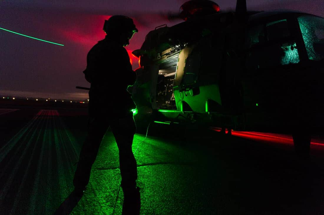 Side view of MRH90 (MRH Taipan) on the tarmac before take-off. Aircrewman is in silhouette, back-lit by the green lights on the MRH. The doors of the helicopter are open and you can see inside the cabin as it is brightly lit. The red and green lights on the base of the helicopter are casting light onto the military helicopter. The green tip lights of the MRH are visible, showing the rotor blades are turning.