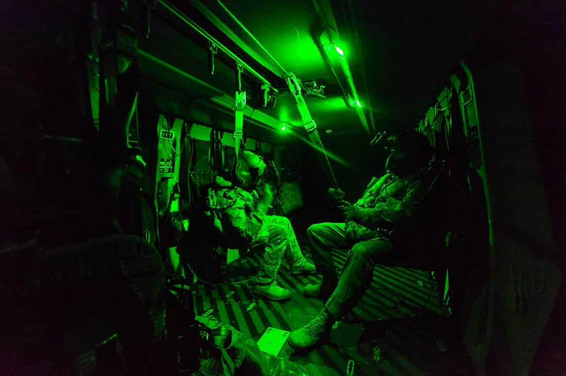 Interior of a military helicopter MRH90 Taipan lit entirely by green light, showing two aircrewmen attached to the airframe by high tensile lanyards. They are seated and have helmets on, with night vision goggles attached to them. One sitting on each side of the aircraft.